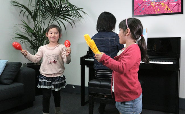 two children playing musical games with the piano